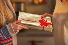 Κινηματογράφηση σε πρώτο πλάνο σε δύο φίλες που ανταλλάσσουν τα χριστουγεννιάτικα δώρα Στοκ φωτογραφία με δικαίωμα ελεύθερης χρήσης