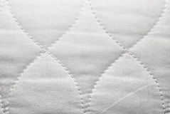 Κινηματογράφηση σε πρώτο πλάνο στην άσπρη διαμορφωμένη κλεψύδρα σύσταση υποβάθρου υφάσματος Στοκ Φωτογραφία