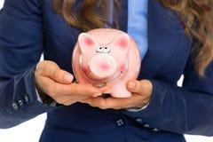 Κινηματογράφηση σε πρώτο πλάνο στην επιχειρησιακή γυναίκα που δίνει τη piggy τράπεζα σίτισης με το νόμισμα Στοκ φωτογραφίες με δικαίωμα ελεύθερης χρήσης