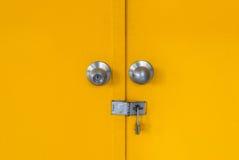 Κινηματογράφηση σε πρώτο πλάνο στην κλειδωμένη κίτρινη πόρτα μετάλλων Στοκ Φωτογραφία