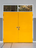 Κινηματογράφηση σε πρώτο πλάνο στην κλειδωμένη κίτρινη πόρτα μετάλλων με το παράθυρο γυαλιού Στοκ Φωτογραφία