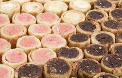 Κινηματογράφηση σε πρώτο πλάνο στη βανίλια, τη φράουλα, και το υπόβαθρο ρόλων μπισκότων σοκολάτας Στοκ εικόνα με δικαίωμα ελεύθερης χρήσης