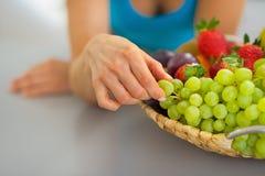 Κινηματογράφηση σε πρώτο πλάνο στη γυναίκα με το πιάτο φρούτων που τρώει το σταφύλι Στοκ φωτογραφίες με δικαίωμα ελεύθερης χρήσης