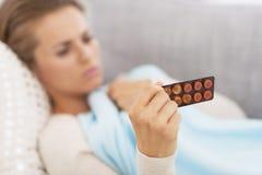 Κινηματογράφηση σε πρώτο πλάνο στη συσκευασία φουσκαλών ιατρικής υπό εξέταση του αισθήματος της κακής γυναίκας Στοκ Φωτογραφία