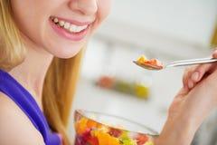 Κινηματογράφηση σε πρώτο πλάνο στη χαμογελώντας νέα γυναίκα που τρώει τη σαλάτα φρούτων Στοκ Εικόνες