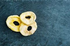 Κινηματογράφηση σε πρώτο πλάνο στις ξηρές φέτες μήλων στο υπόστρωμα πετρών Στοκ Εικόνες