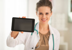 Κινηματογράφηση σε πρώτο πλάνο στο γιατρό που παρουσιάζει στο PC ταμπλετών κενή οθόνη Στοκ Εικόνες