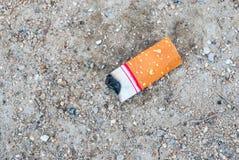 Κινηματογράφηση σε πρώτο πλάνο στο κοντό στέλεχος τσιγάρων στο έδαφος Στοκ εικόνα με δικαίωμα ελεύθερης χρήσης