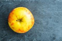Κινηματογράφηση σε πρώτο πλάνο στο μήλο στο υπόστρωμα πετρών Στοκ Φωτογραφίες