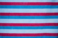 Κινηματογράφηση σε πρώτο πλάνο στο οριζόντιο άσπρο μπλε και κόκκινο ριγωτό υπόβαθρο υφάσματος Στοκ Εικόνα