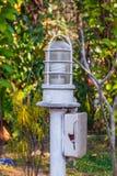 Κινηματογράφηση σε πρώτο πλάνο στο υπαίθριο σπασμένο κιβώτιο συνδέσεων με τον άσπρο λαμπτήρα στον κήπο Στοκ Εικόνες
