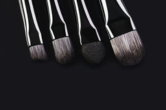 Κινηματογράφηση σε πρώτο πλάνο τεσσάρων βουρτσών makeup σε ένα μαύρο υπόβαθρο οριζόντιος Στοκ Φωτογραφίες