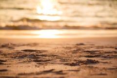 Κινηματογράφηση σε πρώτο πλάνο της άμμου παραλιών ηλιοβασιλέματος με τη σύσταση Θάλασσα στο υπόβαθρο, χρυσό φως του ήλιου Στοκ εικόνα με δικαίωμα ελεύθερης χρήσης