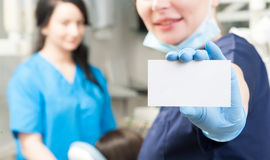Κινηματογράφηση σε πρώτο πλάνο της άσπρης λαβής καρτών από τον οδοντίατρο γυναικών Στοκ Φωτογραφίες