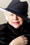 Κινηματογράφηση σε πρώτο πλάνο της άσπρος-μαλλιαρής γυναίκας στο μαύρο καπέλο Στοκ Εικόνα