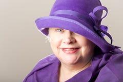 Κινηματογράφηση σε πρώτο πλάνο της άσπρος-μαλλιαρής γυναίκας στο πορφυρό καπέλο Στοκ Εικόνες