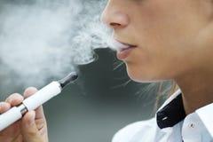 Κινηματογράφηση σε πρώτο πλάνο της γυναίκας που καπνίζει το ηλεκτρονικό τσιγάρο υπαίθριο Στοκ Εικόνες