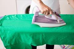 Κινηματογράφηση σε πρώτο πλάνο της γυναίκας που σιδερώνει την πράσινη μπλούζα Στοκ εικόνες με δικαίωμα ελεύθερης χρήσης