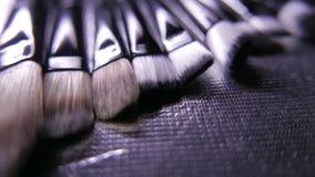 Κινηματογράφηση σε πρώτο πλάνο της εξάρτησης βουρτσών καλλυντικών makeup στην κίνηση 4k UHD απόθεμα βίντεο