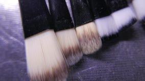 Κινηματογράφηση σε πρώτο πλάνο της εξάρτησης βουρτσών καλλυντικών makeup στην κίνηση 4k UHD φιλμ μικρού μήκους