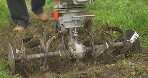Κινηματογράφηση σε πρώτο πλάνο της λεπίδας αρότρων μηχανών χεριών που ρίχνει το έδαφος και τη χλόη νεφελώδης φιλμ μικρού μήκους