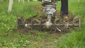 Κινηματογράφηση σε πρώτο πλάνο της λεπίδας αρότρων μηχανών χεριών που ρίχνει το έδαφος και τη χλόη κίνηση αργή φιλμ μικρού μήκους