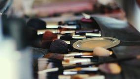 Κινηματογράφηση σε πρώτο πλάνο της επαγγελματικής εξάρτησης βουρτσών καλλυντικών makeup στην κίνηση απόθεμα βίντεο