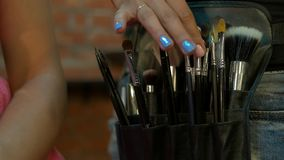 Κινηματογράφηση σε πρώτο πλάνο της επαγγελματικής εξάρτησης βουρτσών καλλυντικών makeup στην κίνηση φιλμ μικρού μήκους