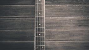 Κινηματογράφηση σε πρώτο πλάνο της κιθάρας που βρίσκεται στο εκλεκτής ποιότητας ξύλο Στοκ φωτογραφία με δικαίωμα ελεύθερης χρήσης