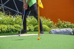Κινηματογράφηση σε πρώτο πλάνο της μικροσκοπικής τρύπας γκολφ με το ρόπαλο και τη σφαίρα Στοκ Εικόνες