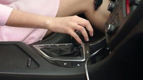 Κινηματογράφηση σε πρώτο πλάνο της νέας γυναίκας που μετατοπίζει το κιβώτιο ταχυτήτων στο αυτοκίνητο απόθεμα βίντεο