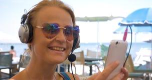 Κινηματογράφηση σε πρώτο πλάνο της νέας γυναίκας στα ακουστικά που μιλούν πέρα από το τηλέφωνο απόθεμα βίντεο