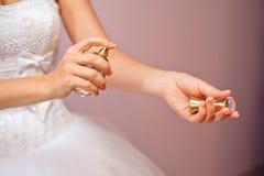 Κινηματογράφηση σε πρώτο πλάνο της νέας νύφης που παίρνει έτοιμη με τα αρώματα στο σπίτι το πρωί Στοκ φωτογραφία με δικαίωμα ελεύθερης χρήσης