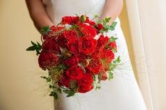 Νύφη που κρατά την κόκκινη ανθοδέσμη τριαντάφυλλων στοκ φωτογραφίες