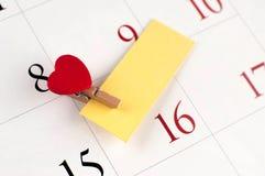 Κινηματογράφηση σε πρώτο πλάνο της ξύλινης καρφίτσας με την καρδιά στην ημερολογιακή σελίδα Στοκ Εικόνες