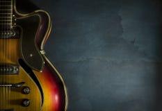 Κινηματογράφηση σε πρώτο πλάνο της παλαιάς ηλεκτρικής κιθάρας τζαζ σε ένα σκούρο μπλε υπόβαθρο στοκ φωτογραφία