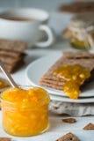 Κινηματογράφηση σε πρώτο πλάνο της πορτοκαλιάς μαρμελάδας στο βάζο γυαλιού και των καφετιών κροτίδων ψωμιού σίκαλης τραγανών σουη Στοκ εικόνες με δικαίωμα ελεύθερης χρήσης