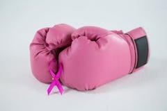 Κινηματογράφηση σε πρώτο πλάνο της ρόδινης κορδέλλας συνειδητοποίησης καρκίνου του μαστού με τα εγκιβωτίζοντας γάντια Στοκ Φωτογραφίες