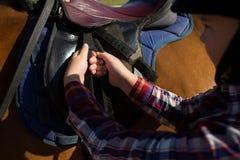 Κινηματογράφηση σε πρώτο πλάνο της σέλας ρύθμισης κοριτσιών στο άλογο Στοκ Εικόνες