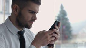 Κινηματογράφηση σε πρώτο πλάνο της συγκεντρωμένης ανάγνωσης νεαρών άνδρων από το smartphone Στοκ φωτογραφία με δικαίωμα ελεύθερης χρήσης