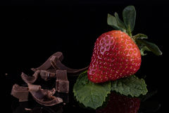 Κινηματογράφηση σε πρώτο πλάνο της φράουλας με τα φύλλα μεντών και της σοκολάτας στο μαύρο BA Στοκ Φωτογραφία