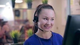 Κινηματογράφηση σε πρώτο πλάνο της χαμογελώντας γυναίκας που λειτουργεί σε ένα τηλεφωνικό κέντρο ο άγγελος ως όμορφη επιχειρηματί φιλμ μικρού μήκους
