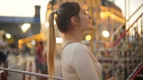 Κινηματογράφηση σε πρώτο πλάνο της όμορφης κομψής γυναίκας που εξετάζει το εύθυμος-πηγαίνω-στρογγυλό ιπποδρόμιο στο βράδυ απόθεμα βίντεο