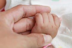Κινηματογράφηση σε πρώτο πλάνο του δάχτυλου του πατέρα εκμετάλλευσης χεριών μωρών στο άσπρο υπόβαθρο στοκ φωτογραφία