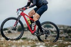 Κινηματογράφηση σε πρώτο πλάνο του αθλητή mountainbiker και του αθλητικού ποδηλάτου που συναγωνίζεται στο μπουκάλι νερό Στοκ εικόνα με δικαίωμα ελεύθερης χρήσης
