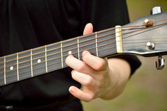 Κινηματογράφηση σε πρώτο πλάνο του λαιμού κιθάρων με το παιχνίδι κιθαριστών Στοκ εικόνα με δικαίωμα ελεύθερης χρήσης