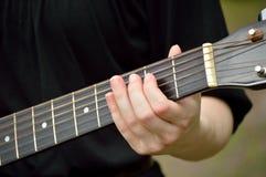 Κινηματογράφηση σε πρώτο πλάνο του λαιμού κιθάρων με το παιχνίδι κιθαριστών Στοκ Εικόνες
