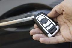 Κινηματογράφηση σε πρώτο πλάνο του αρσενικού χεριού που κρατά το μακρινό κλειδί αυτοκινήτων Στοκ Εικόνες