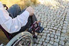 Κινηματογράφηση σε πρώτο πλάνο του αρσενικού χεριού στη ρόδα της αναπηρικής καρέκλας στοκ φωτογραφίες