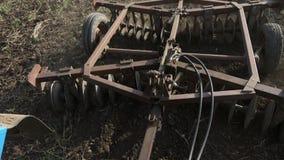 Κινηματογράφηση σε πρώτο πλάνο του αρότρου που συνδέεται με ένα τρακτέρ που οργώνει έναν τομέα απόθεμα βίντεο